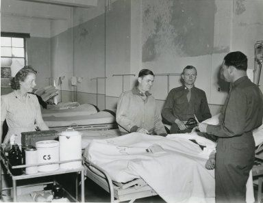 Doctors and Nurse Checking on Patient in Hospital Ward, from 25th General Hospital: Courage & Skill in World War II -- for an exhibit highlighting movements, personal     narratives and medical contributions see http://digitalprojects.libraries.uc.edu/exhibits/25thGeneralHospital/;     for entire collection see http://digproj.libraries.uc.edu:8180/luna/servlet/s/4lcgzb; connect on Facebook and     share your own WWII General Hospital stories at http://www.facebook.com/UC25thGeneralHospital.