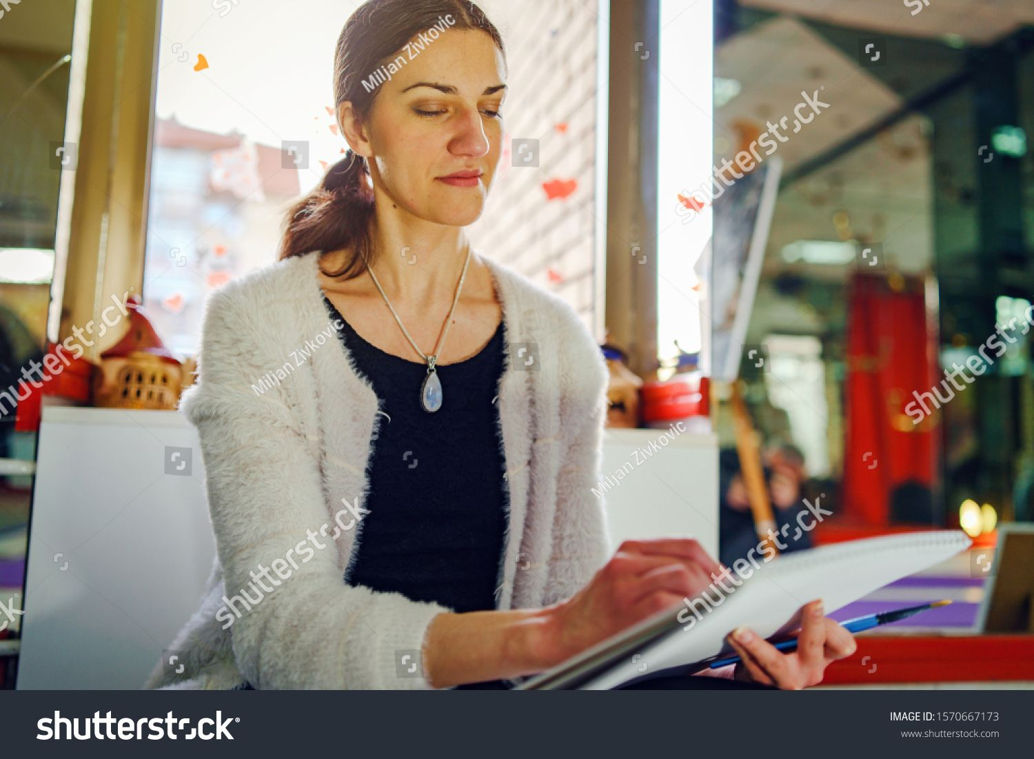 Portrait of young woman sitting and drawing or painting making art by the window at home or studio #Ad , #AD, #sitting#drawing#woman#Portrait