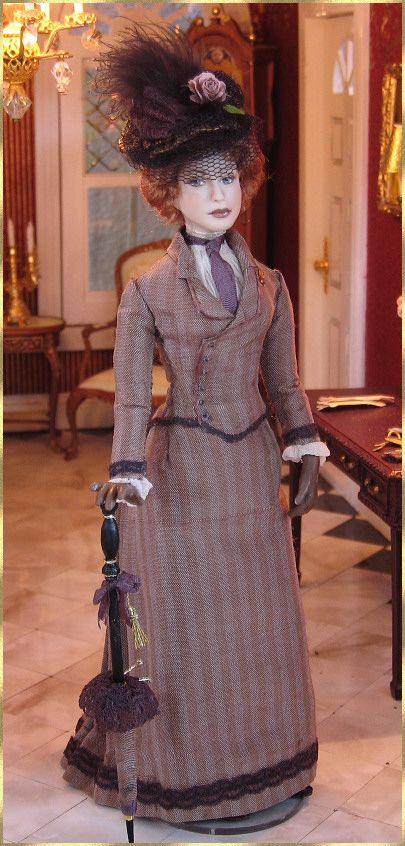 She is wearing a 1890's  fashionable Parisian  suit-dress, made of striped silk.
