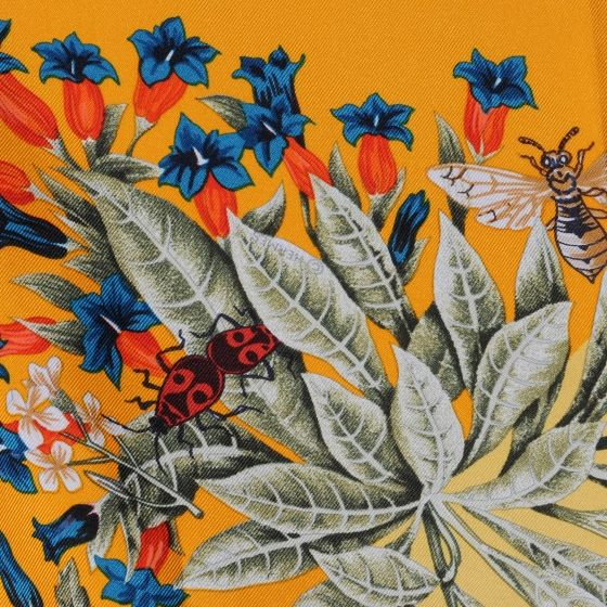 This is an authentic HERMES Silk La Prairie Scarf 90. This chic scarf is 100 silk and features a bright flora pattern on a gold ground.