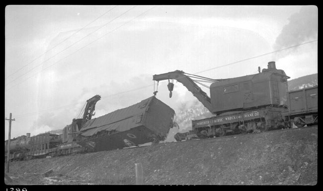 """Caption: """"Two wreckers are picking up an iced refrigerator car from of derailment of 19 cars from Train No. 603 at Turah, MT, MP 109.6, between Clinton and Bonner, MT. Wreckers are NP 37 on the right and NP 23 on the left."""" Date: January 1933 Location: Turah, MT Photographer: Ron V. Nixon Railroad: Northern Pacific Railway Station: Turah ---- USA"""