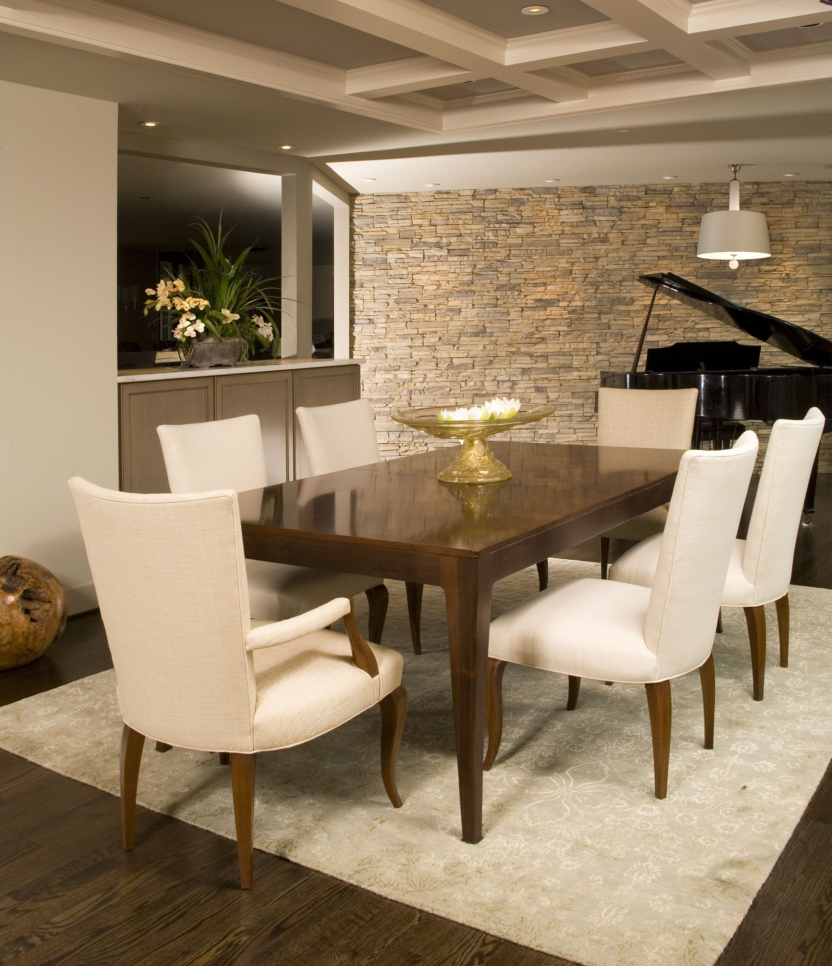 Modern dining room with clean lines and neutral stone wall