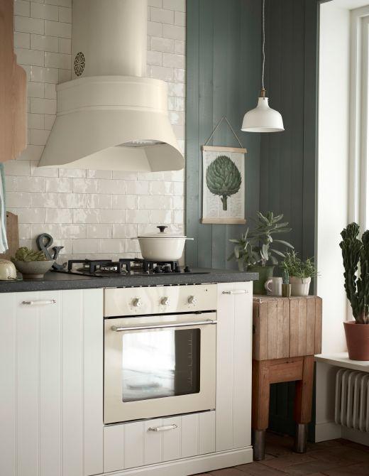 Cocina blanca con un extractor grande beige encima de una placa de ...