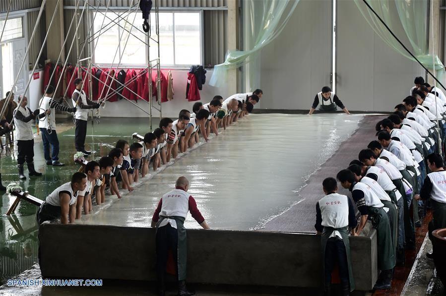 ANHUI, noviembre 21, 2016 (Xinhua) -- Trabajadores elaboran súper papel Xuan en un taller del condado de Jingxian, en la ciudad de Xuancheng, en la provincia de Anhui, en el este de China, el 21 de noviembre de 2016. El súper papel Xuan mide 11 metros de longitud y 3.3 metros de anchura, y es elaborado para pintura tradicional a gran escala y creación de caligrafía. El papel Xuan, un tipo de papel hecho a mano, fue originalmente producido durante la Dinastía Tang (618-907) en el condado…