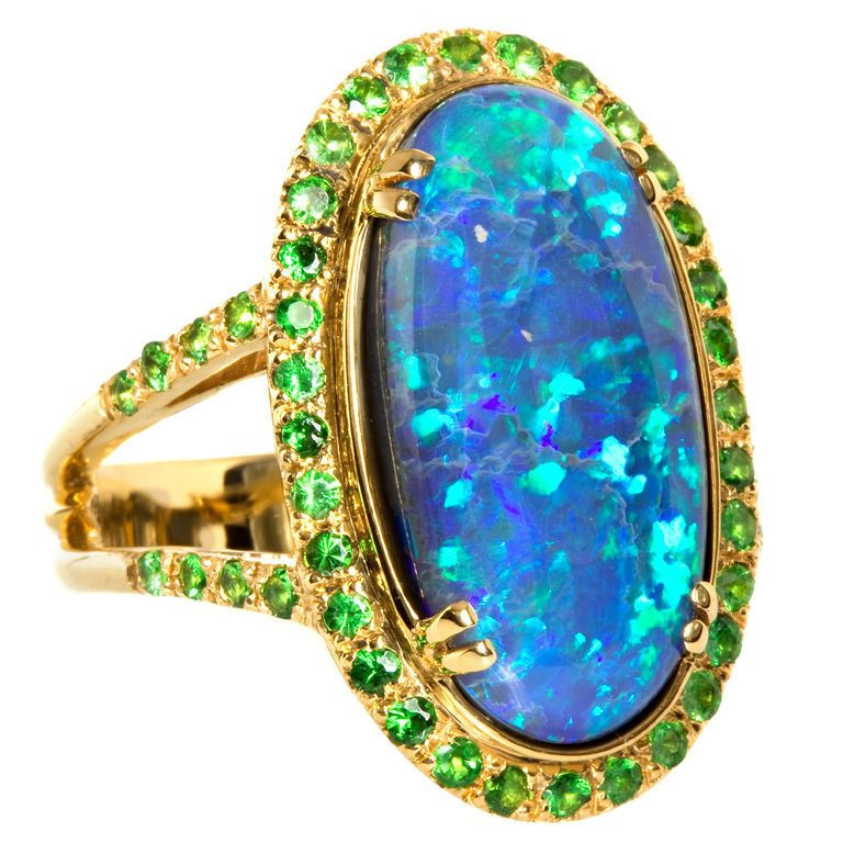 Captivating 10.87 carat Black Opal set with 0.55 carats of vivid green Tsavorite Garnets in 12.1 grams of 18K Yellow Gold.