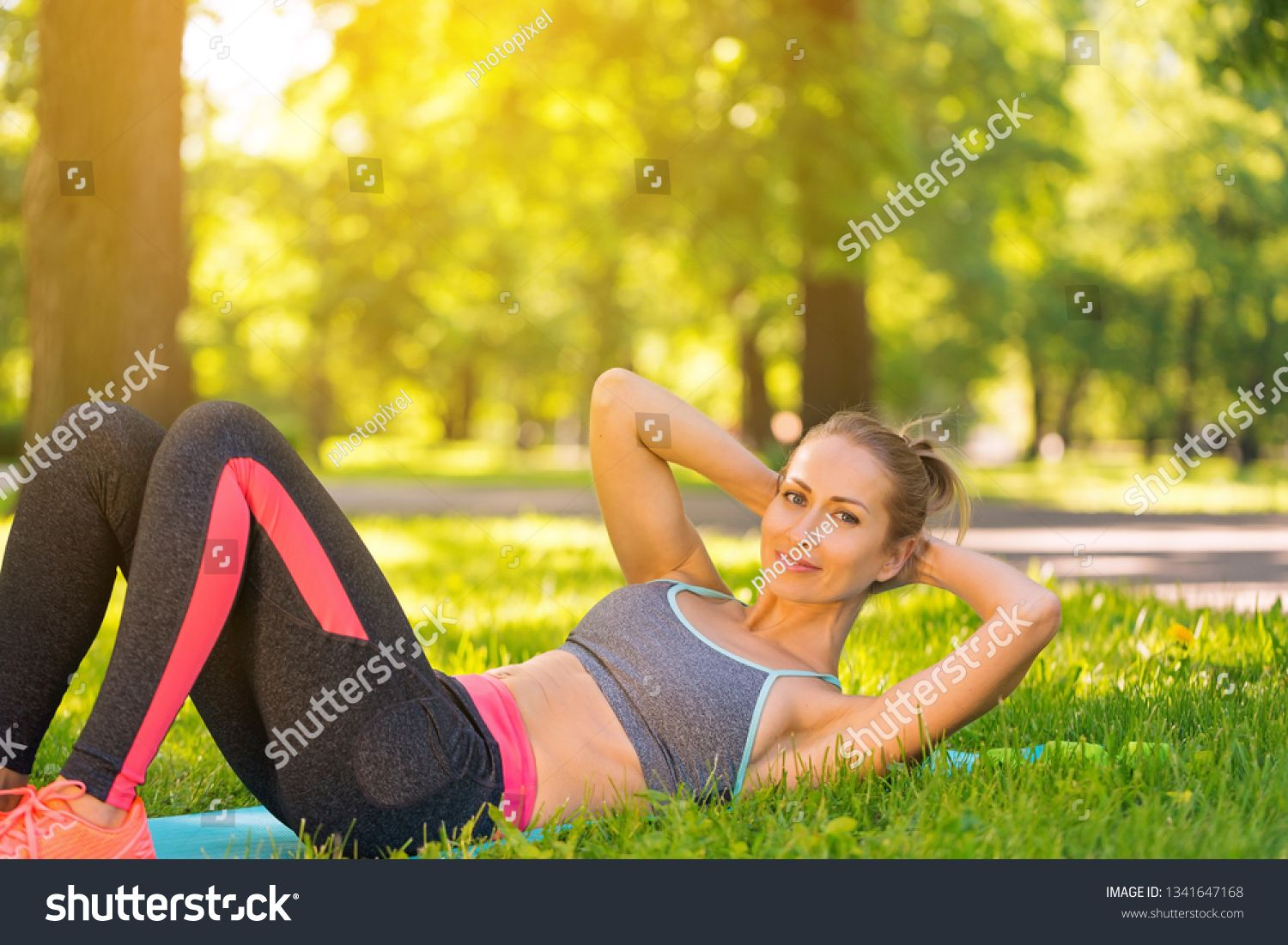 Young fit woman doing abdominal crunch and training outside on green grass at park. Fitness, sport and healthy lifestyle, abs workout ,
