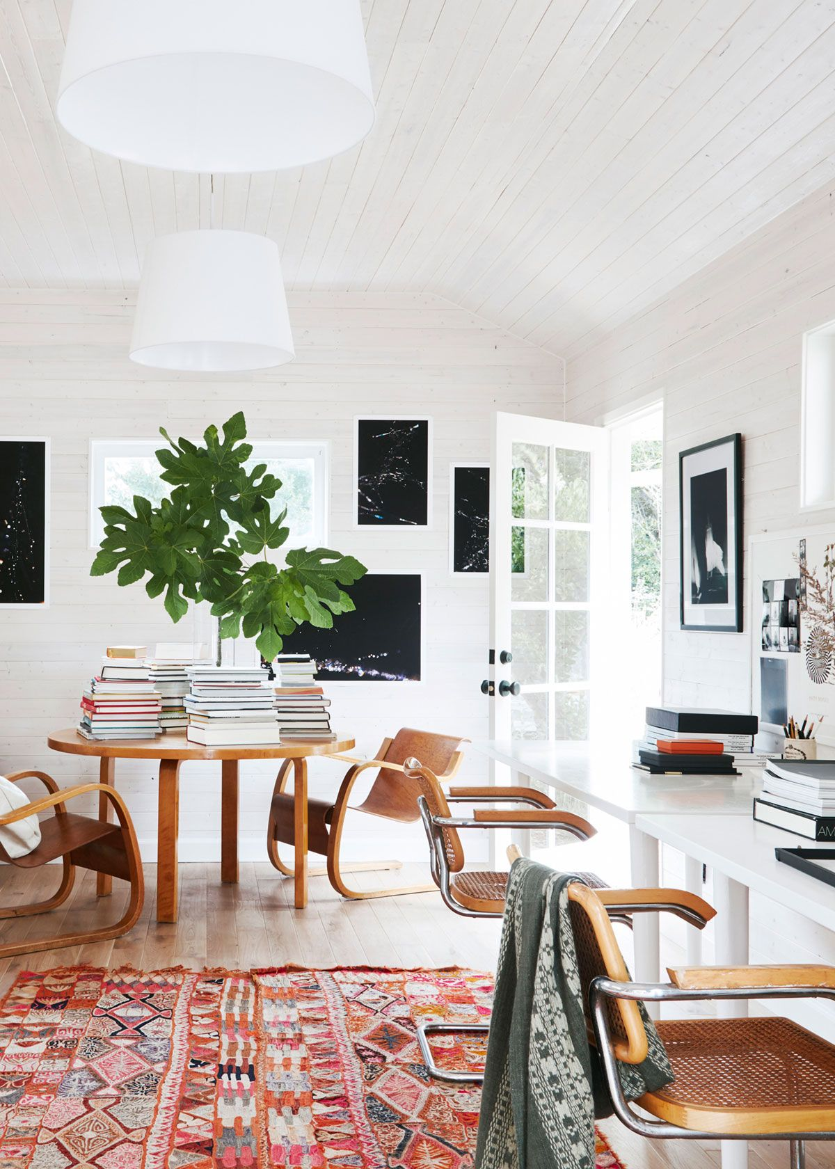 modern home office with white shiplap walls, moroccan area rug, and ...