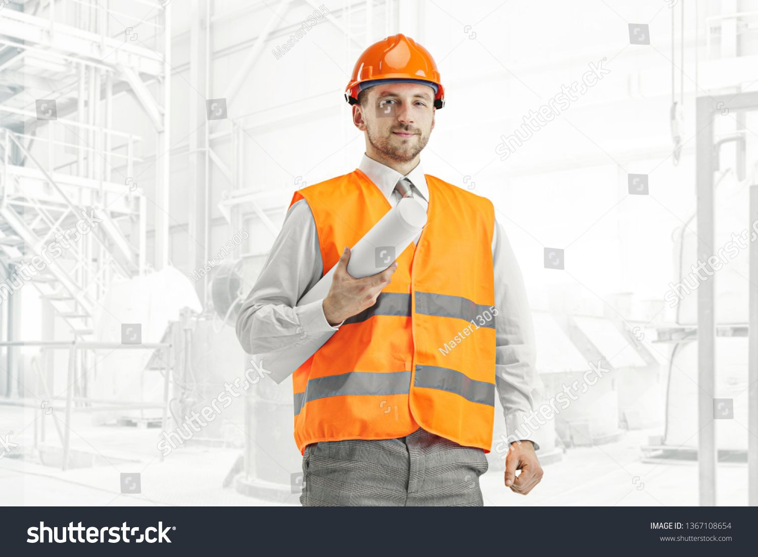 The builder in a construction vest and orange helmet
