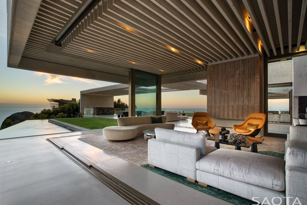 OVD 919 by SAOTA. The summer lounge overlooks the Atlantic Ocean. This picture captures the perfect sunset. This contemporary Cape Town home is situated below the iconic Lions Head. The architecture for the modern villa draws strength from the concrete finish used to create monumental forms which contrast to the copper roof . The home is filled with art and design and plays with a contract of wood, concrete and glass.