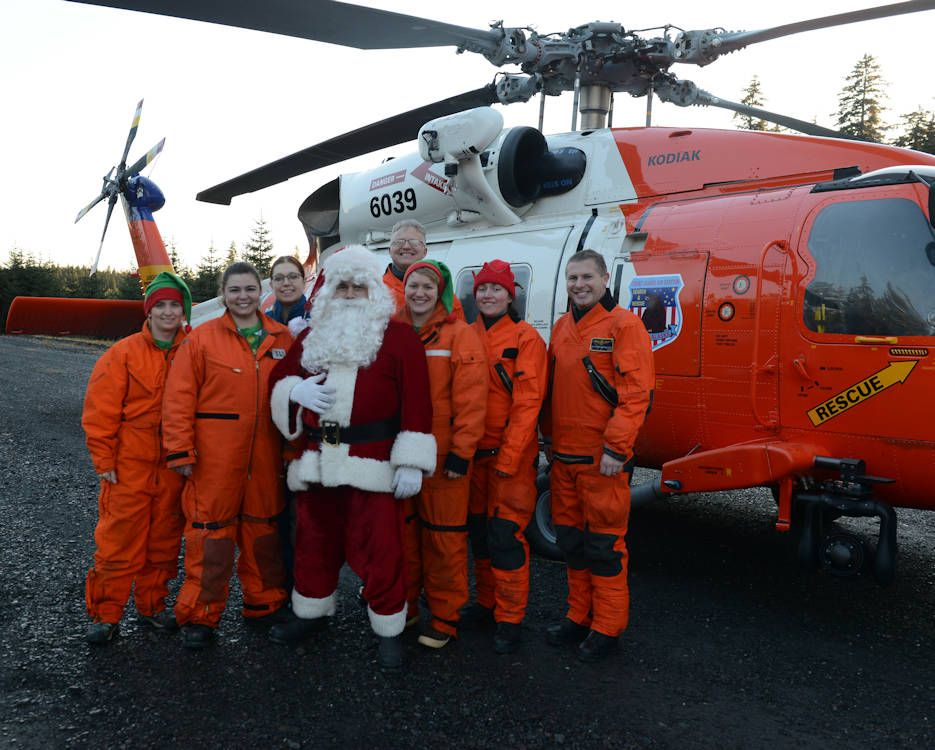 Santa Claus with his Coast Guard elves and the Jayhawk
