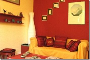 This Room Has A Warm Color Scheme With The Red And Yellow Wall Darker Couch Drape Accent Pillows Help It Feel