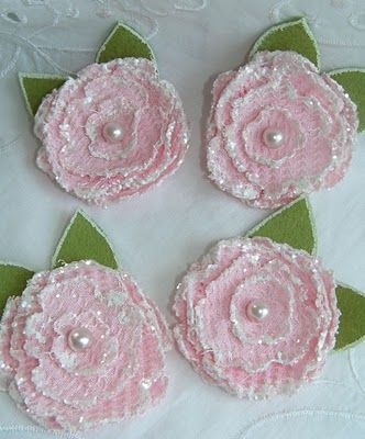 She made these using synthetic fabric and a Sizzix layered flower die, heated the edges with her heat gun, added acrylic paint and glitter. She cut the leaves from felt and also highlighted the edges with paint.