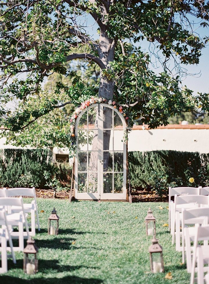 Wedding arbor used old door decorated with floral garland + lantern on aisle , wedding ceremony decoration ideas