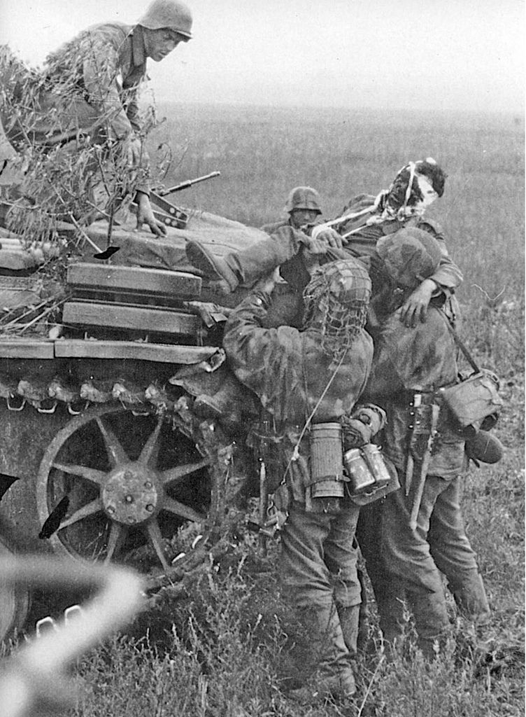 German soldiers carry a wounded comrade onto a waiting tank (either a Panzer III or a StuG III) , somewhere in the eastern front