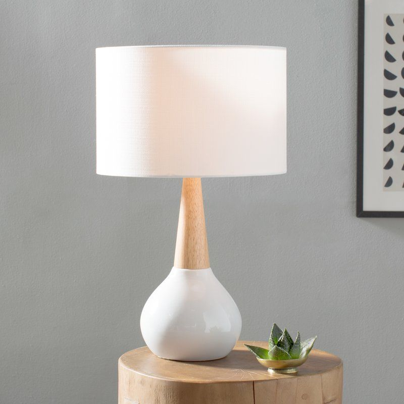 Featuring a white ceramic and wood base with a white linen shade the simple styling of wallin table lamp has a distinctly nordic disposition