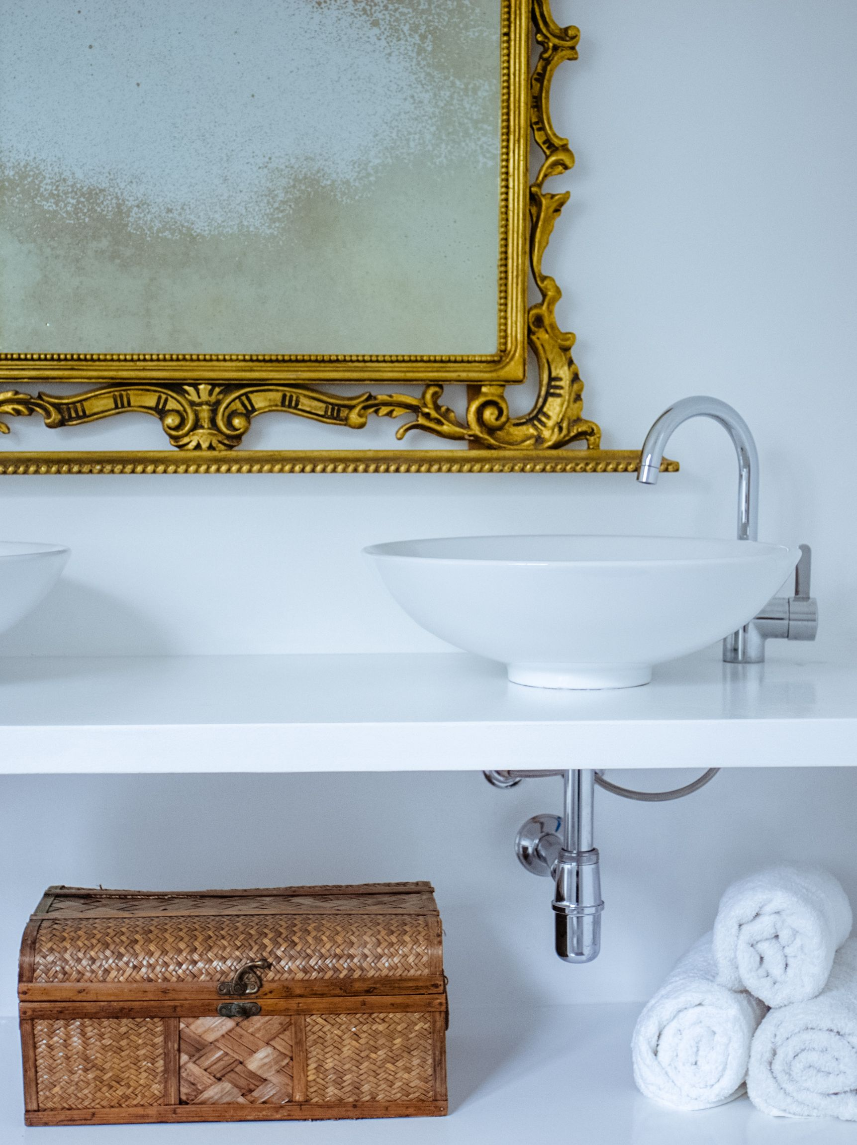 A fabulous gold mirror and a wicker box, both found at the fleamarket add a new dimension to our stunning modern bathroom