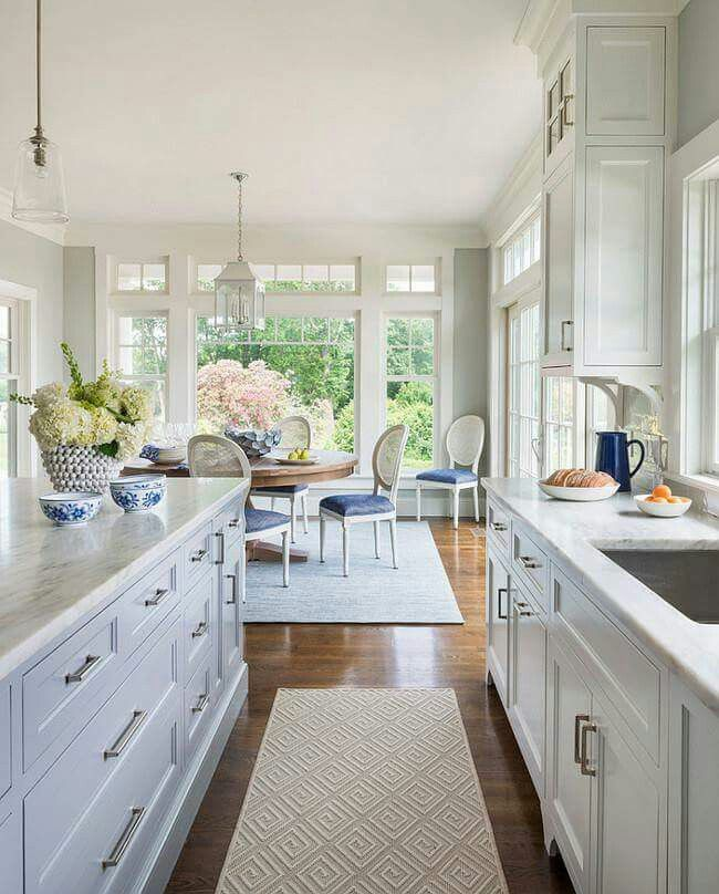 white and grey kitchen features white cabinets paired with white marble countertops fitted with a