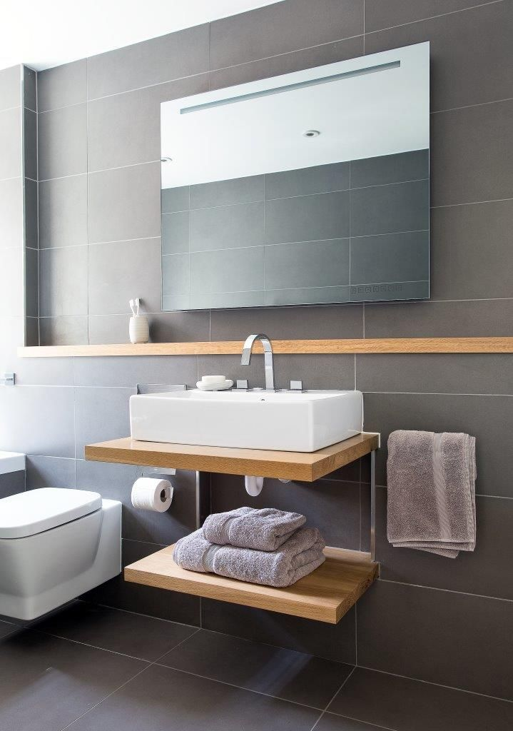 Gorgeous grey stylish bathroom with warm wooden elements to create a