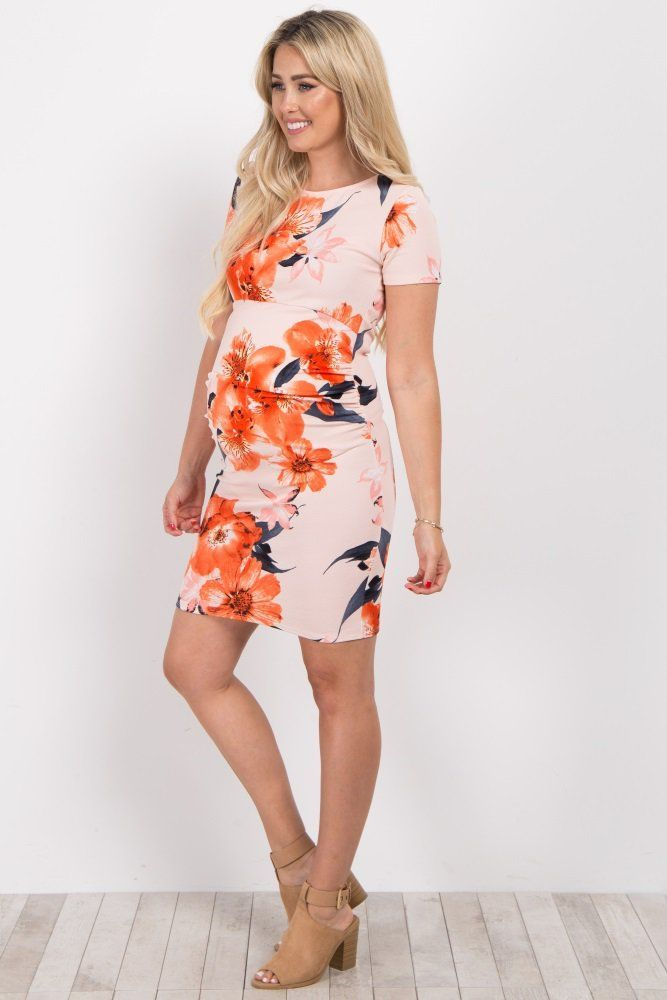 4ca71a225f A floral print short sleeve fitted maternity dress. Ruched sides. Rounded  neckline.