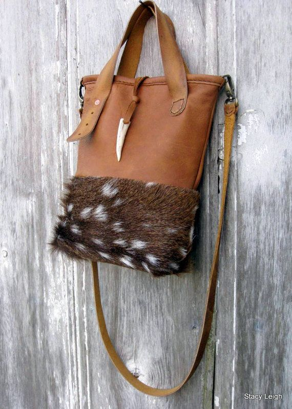 Mini tote bag with detachable 44.5 long strap made from rocky mountain, distressed leather, and hair on, axis deerskin. Bag is 11 tall by 9 across with a 3 bottom. Hand stitched top rim. Fully lined with 1 leather pocket and d-ring for keys. Magnetic snap. White tail, deer antler tip embellishment. Adorable, petite size.