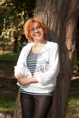 Middle-aged woman smiling near big tree Stock Photo