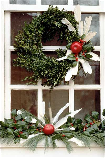 during the holiday season colonial williamsburg doors and windows are wreathed in arrangements fashioned of natural materials this boxwood construction is