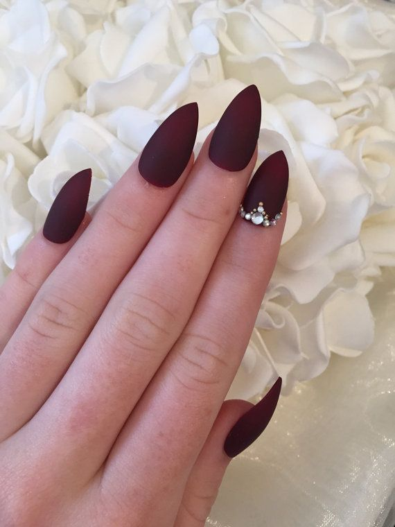 Burgundy matte stiletto nails with rhinestone and gold bead details ...