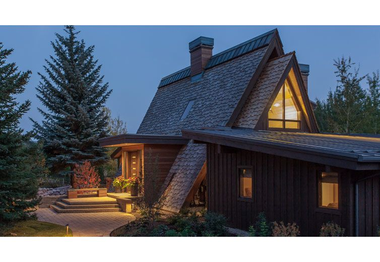 view of the approach and entry at twilight. a contemporary a-frame