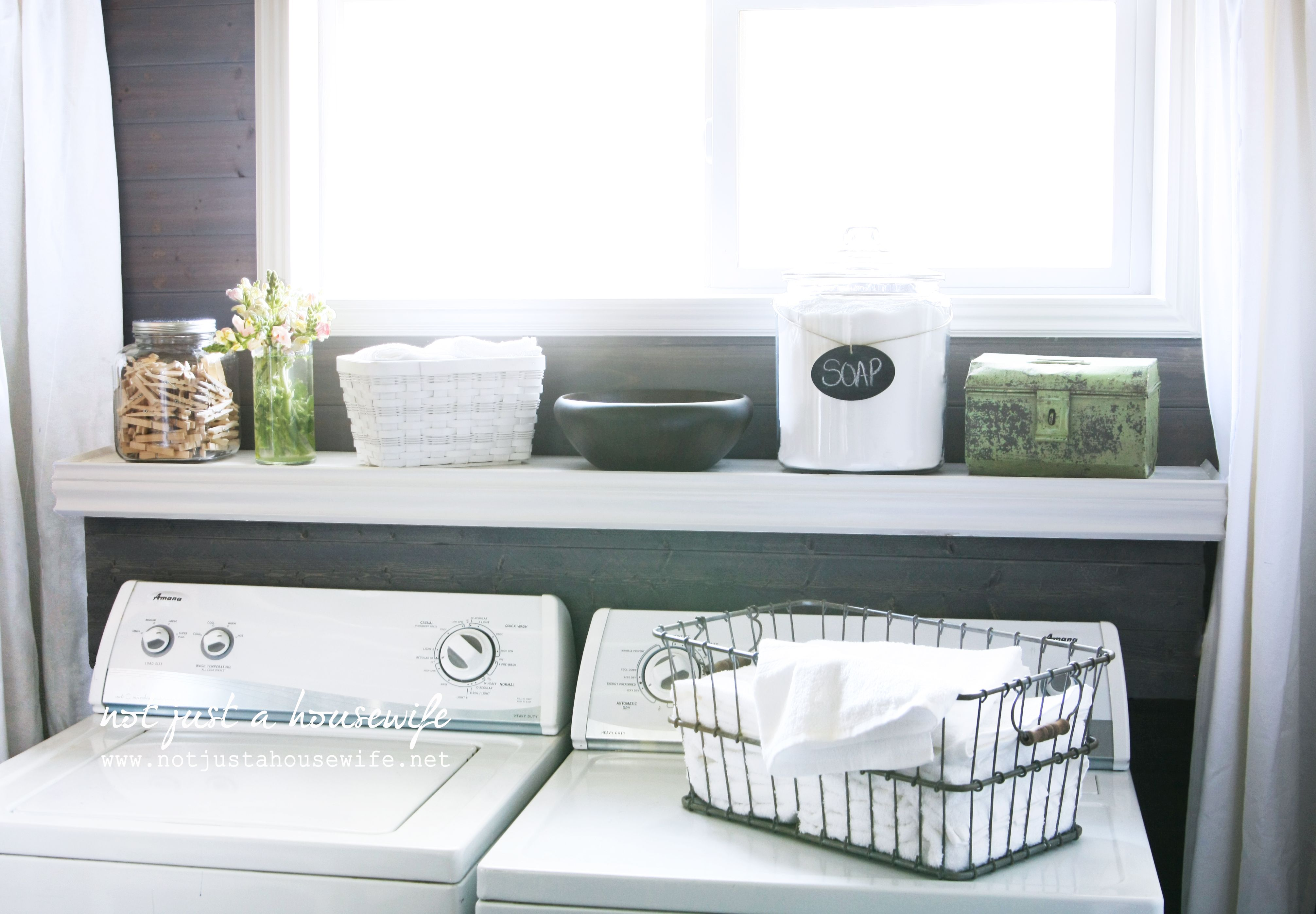 Hinged shelf above a washer and dryer so that you can still get to the plugs and hoses