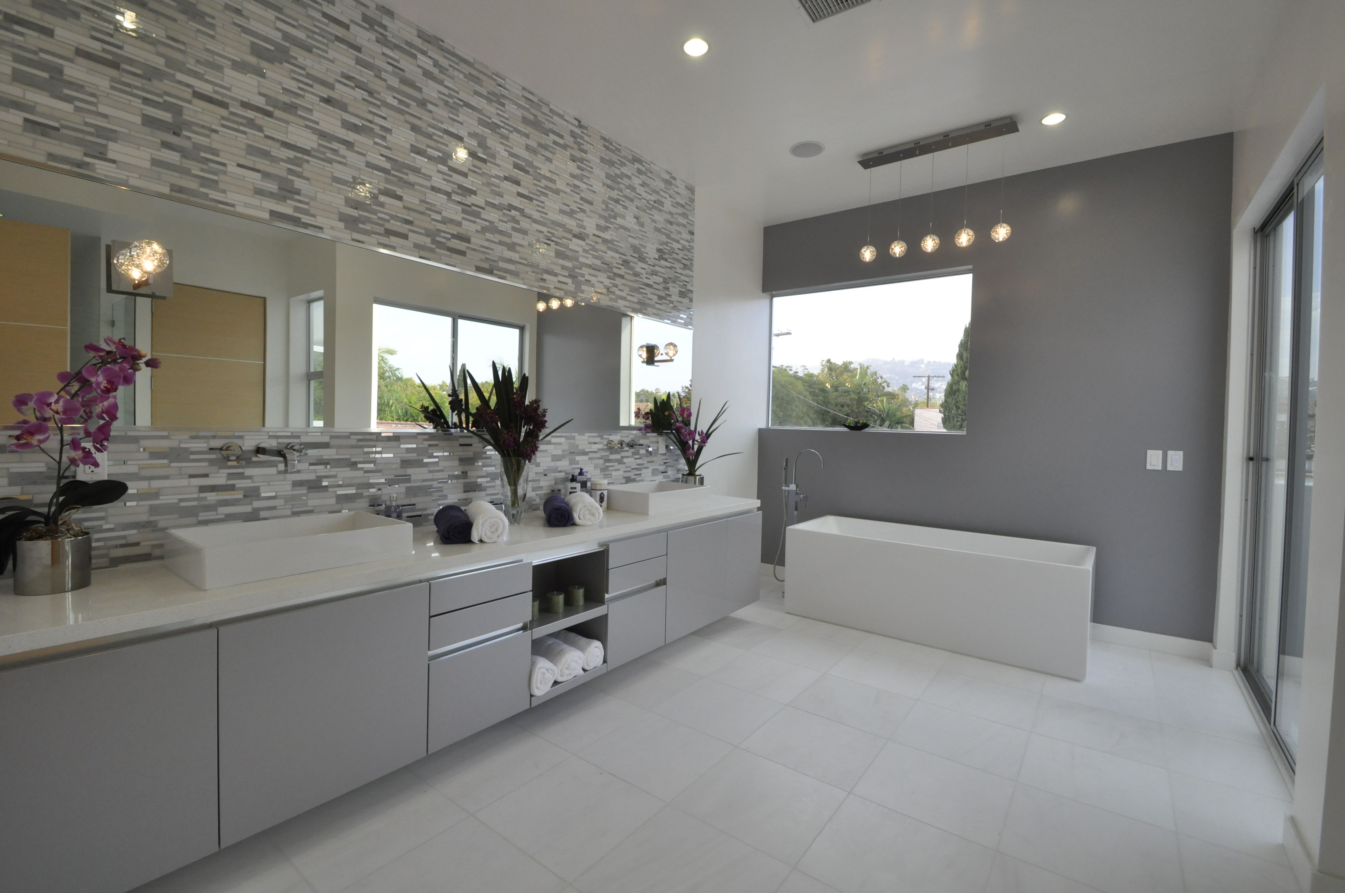 Symmetrical bathroom design is completed with the ET2 Orb lighting fixture.  See this collection at