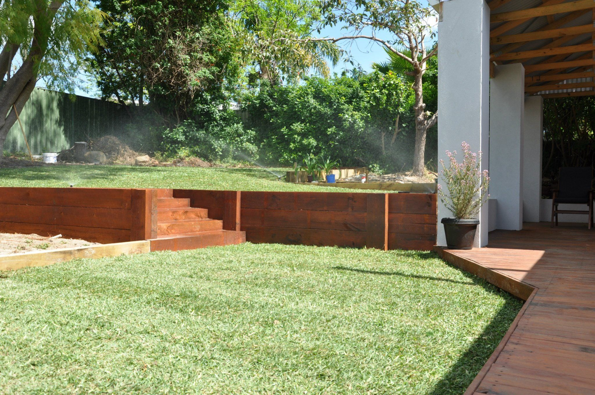 Pine sleeper retaining wall stained with steps leading up to