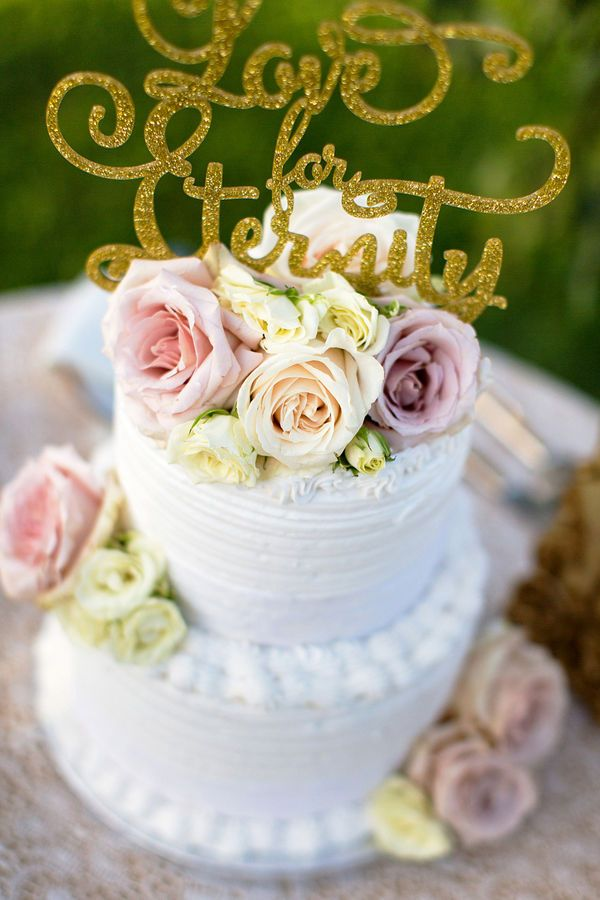 A Calligraphy Gold Glitter Wedding Cake Topper With Blush Roses On Buttercream