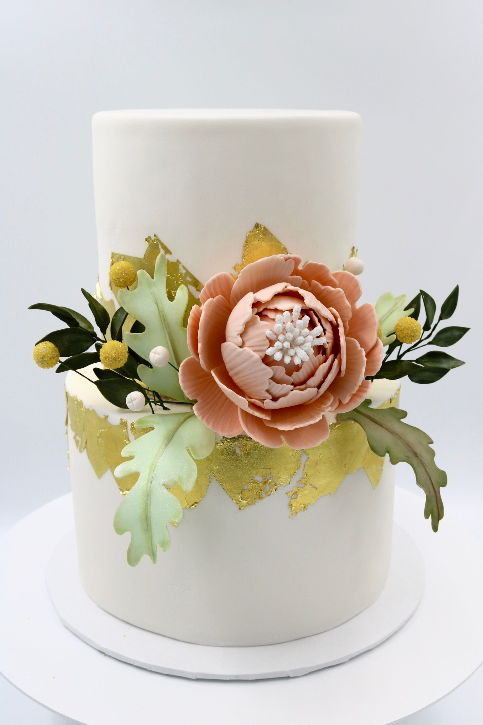 2 tier white cake with gold foil with handmade peach