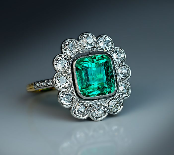 Antique Edwardian Era Old Mine Colombian Emerald and Diamond Engagement Ring. French, circa 1915. This classical cluster ring is finely crafted in platinum over 18K yellow gold. The ring is centered with a superb Colombian emerald (approximately 2.25 ct) set in a platinum milgrain bezel surrounded by 12 old mine cut diamonds. The shoulders are embellished with six rose cut diamonds. Estimated total diamond weight 1.30 ct.