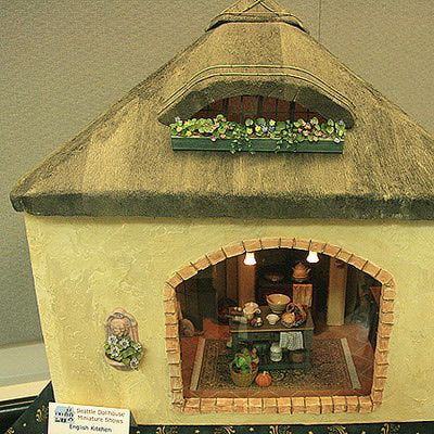 Photos of Roomboxes from the Fall 2010 Seattle Dollhouse Miniature Show: Kitchen roombox with a 'thatched' hipped roof and attic window, exhibited by Mary Lou Johnson at the Fall 2010 Seattle Dollhouse Miniature Show