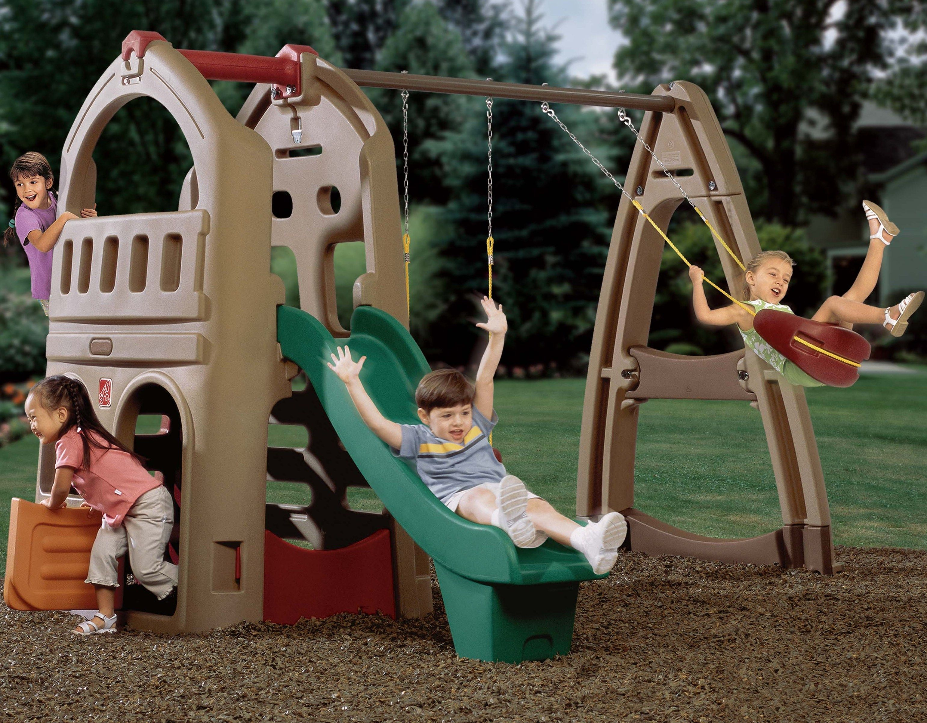 Children's backyard playhouse climber with slide and swing set in natural colors with dutch door and hideaway.