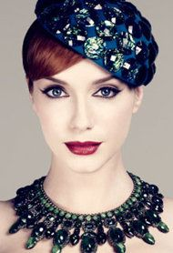 Get Christina Hendricks's Gorgeous Makeup Look | Wet eyeliner brush then use soft grey-black shadow to draw basic structure of wing and fill in lashline. Then liquid liner close to the lash line.  Then soft aubergine eyeliner in the outer corners
