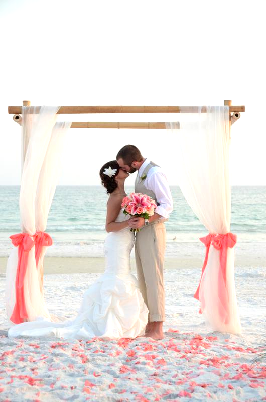 Natural bamboo beach wedding arbor draped curtain style with coral sashes and rose petals in Grayton Beach