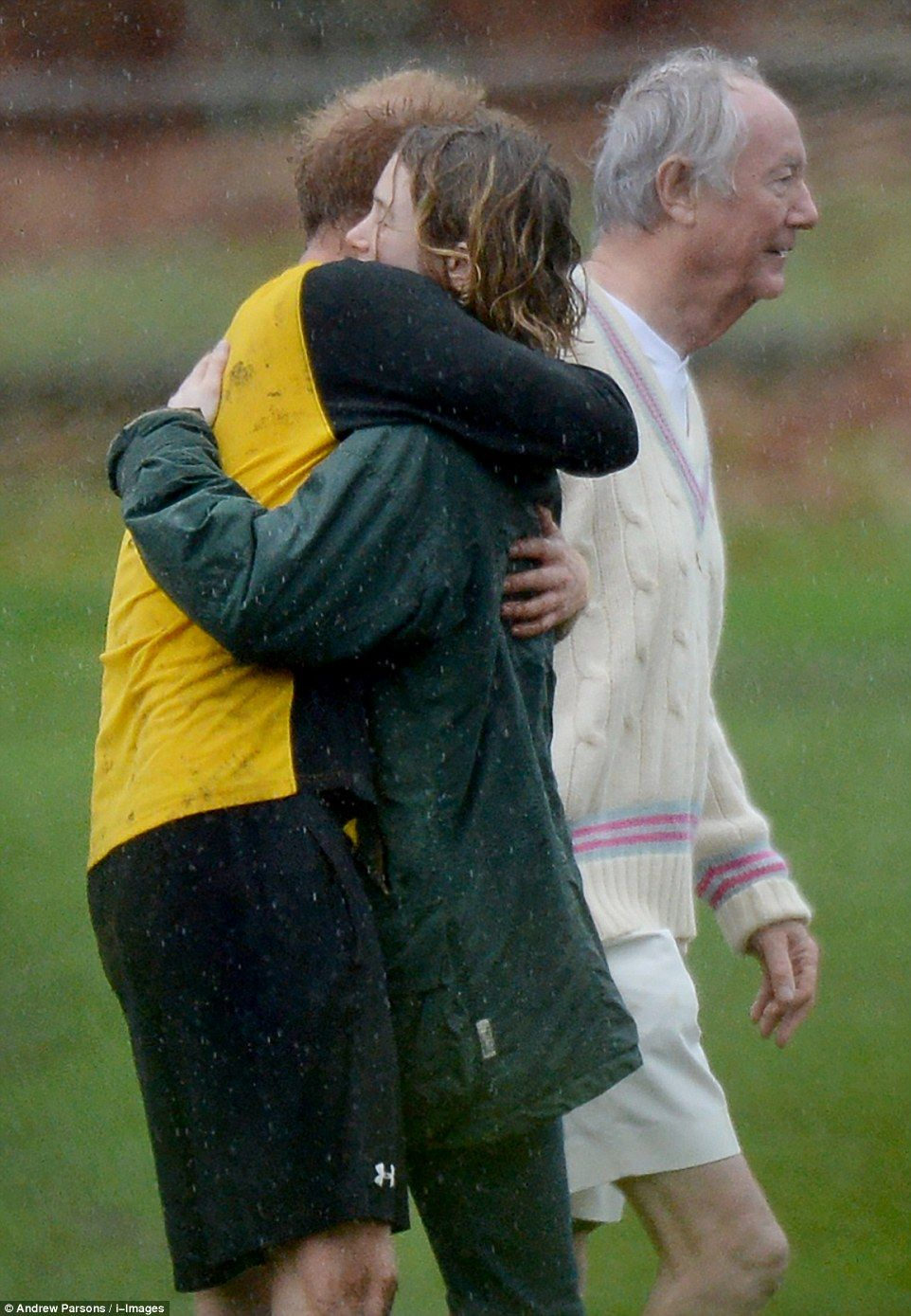 Harry hugs a young girl who had been watching the match who doesn't seem to mind his muddy shirt