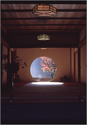 Japanese Styled Room With Round Window Framing A Tree