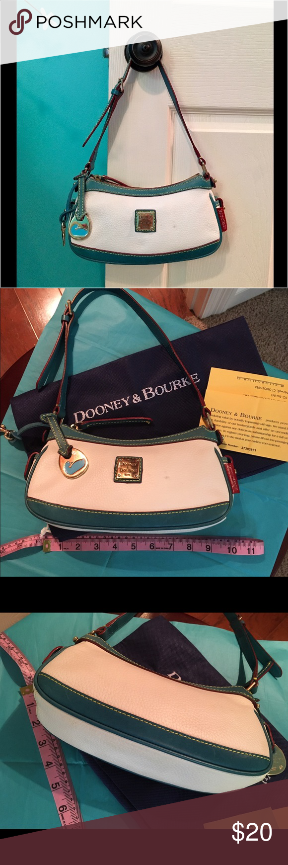 """Dooney & Bourke Leather Mini Bag 9.5 x 5 x 3. Gold plate with Blue Swan Leather chain. Additional Leather key chain inside(outside in pics). Adjustable Leather Strap. Red Leather Label on Side. Red Fabric  inside with zip pocket AND  1 small """"lipstick size"""" pocket inside.🌟🌟🌟🌟NOTE- very faint Grayish/Bluish spots on Front- can probably come off with a Leather cleaner. NO TRADES Dooney & Bourke Bags Mini Bags"""