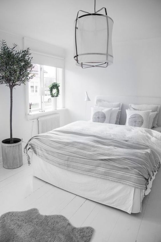 An all white bedroom interior will help make a small bedroom look and feel larger and watch the window blinds and trim and it will blend into the walls even further. #smallbedroom #smallbedroomideas #whitebedroomideas #whitebedroomideassmall #smallbedroominspirations #