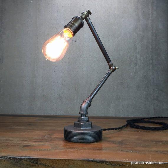 Esta elegante lámpara industrial adapta a una variedad de ambientes incluyendo cualquier oficina o estudio. El accesorio todo es ajustable usando los accesorios de latón envejecido para la perfecta colocación de la bombilla. El alta es totalmente regulable para apenas la cantidad correcta de luz.  Un 60 Edison de la jaula de la ardilla de Watts ofrece sutil pero brillante luz ambiental y se incluye con la lámpara.  Este accesorio está hecho de tubería de hierro negro pesado. La lámpara…