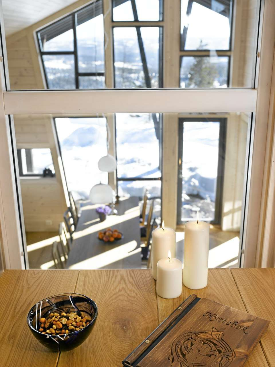 OVERBLIKK OG NÆRKONTAKT: Fra oppholdsrommet på hemsen ser man ned til kjøkkenet og ut gjennom de store vinduene. Dette skaper en kontakt og nærhet mellom rommene.