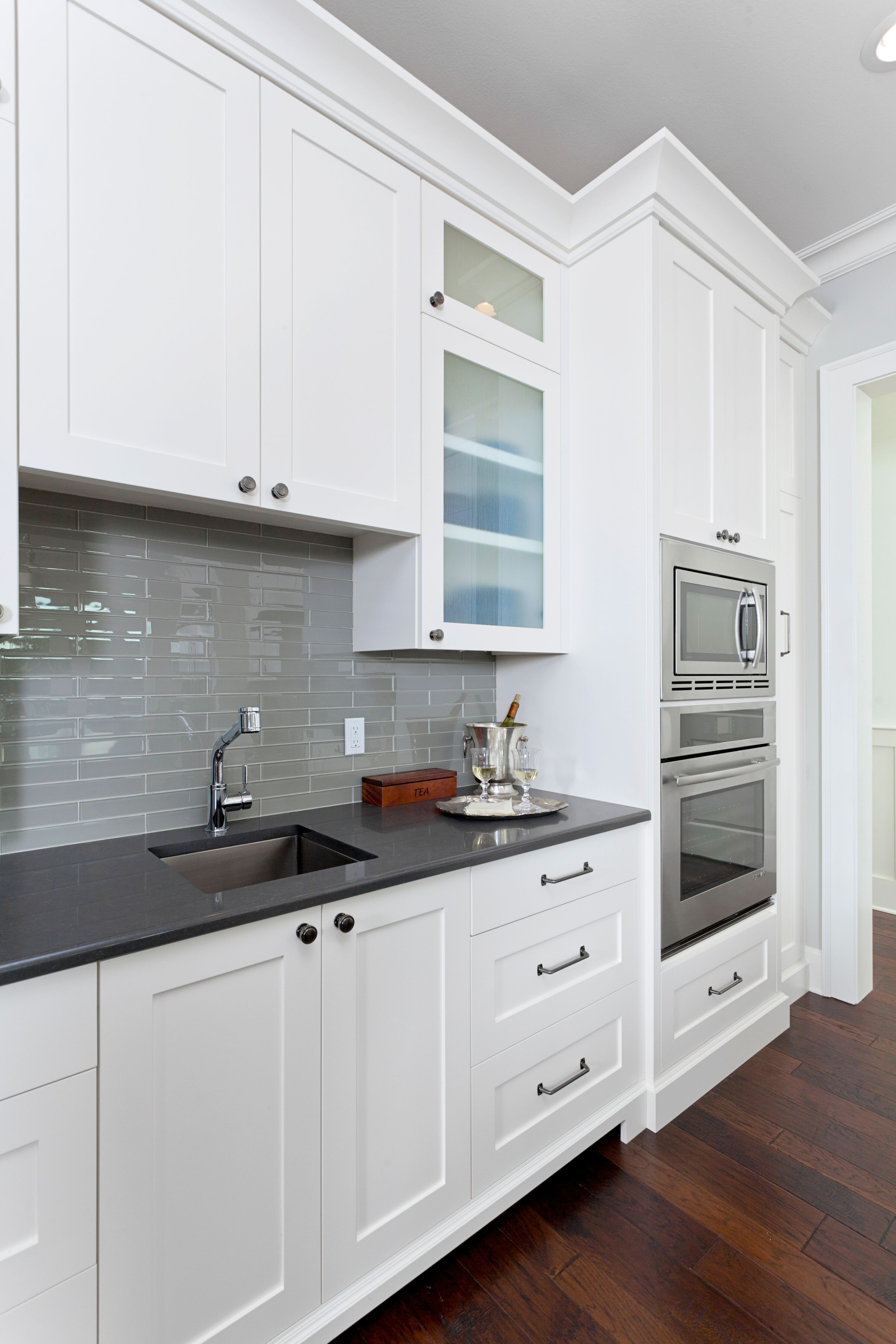 White Kitchen With Dark Counters And Grey Backsplash Designed By In Detail Interiors In Pensacola Fl Whit Kitchen Remodel Grey Backsplash Kitchen Design