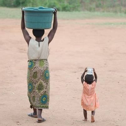 Mother and daughter carrying water.