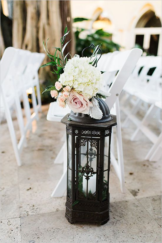 Antique lantern with florals placed on top make the perfect aisle decor.