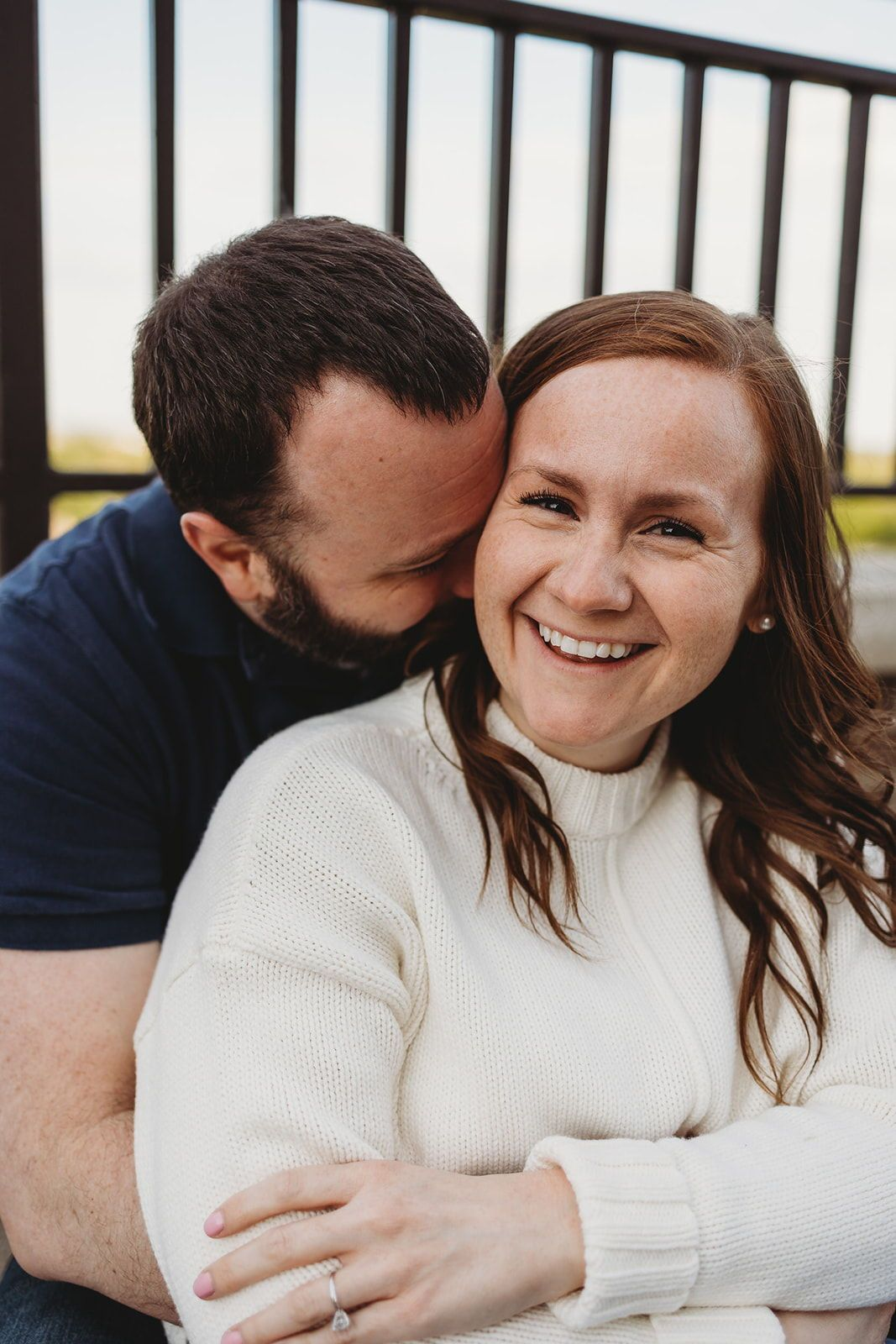 Cute engagement session at western michigan university in park. Perfect inspiration for couples photo shoot poses ideas. Fiance kissing her neck and showing off her engagement ring. Engagement photo shoot inspiration in fall! Traveling Wedding and Couples Photographer. Lindsay Elaine Photography.