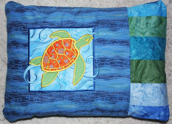Pillow embroidered with sea turtle applique design.
