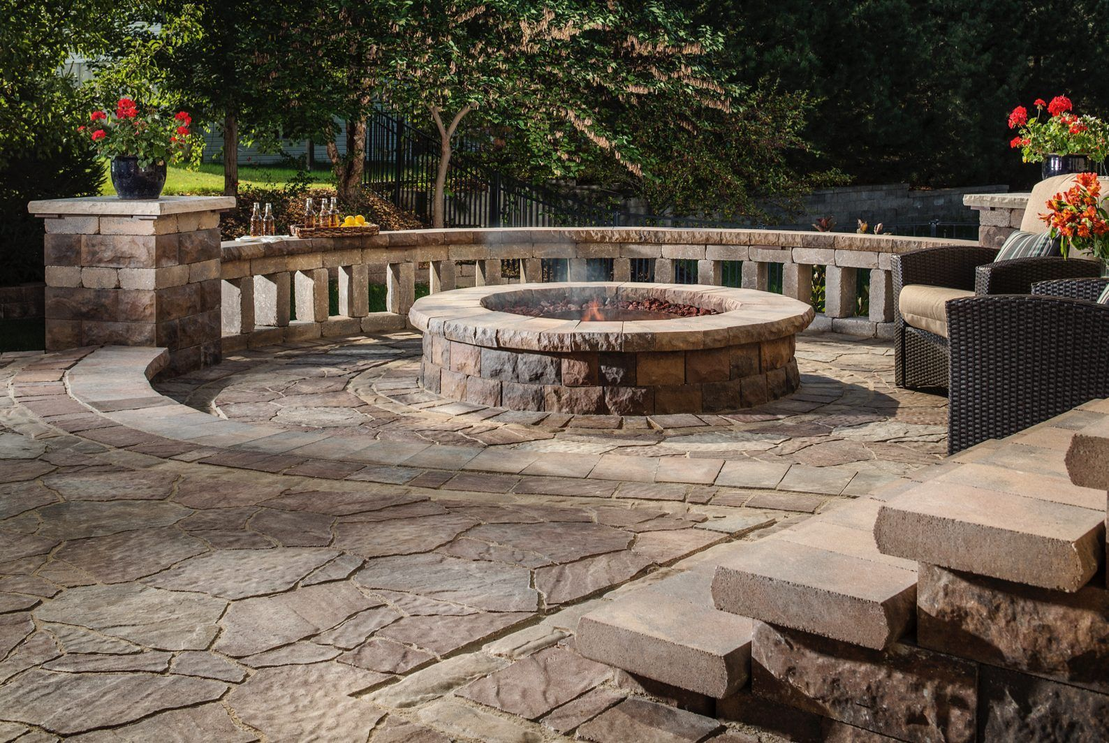 the decorative wall surrounding this fire pit uses mediterranean